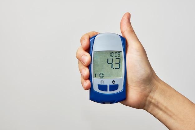 Hand hält glukometer mit blutzuckertestergebnis. frauenhand, die zuckertest zeigt, auf weißem hintergrund mit kopienraum