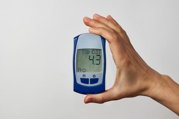Hand hält glukometer mit blutzuckertestergebnis. frauenhand, die zuckertest zeigt