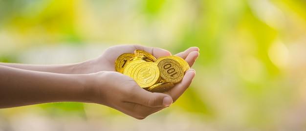 Hand hält goldmünzen
