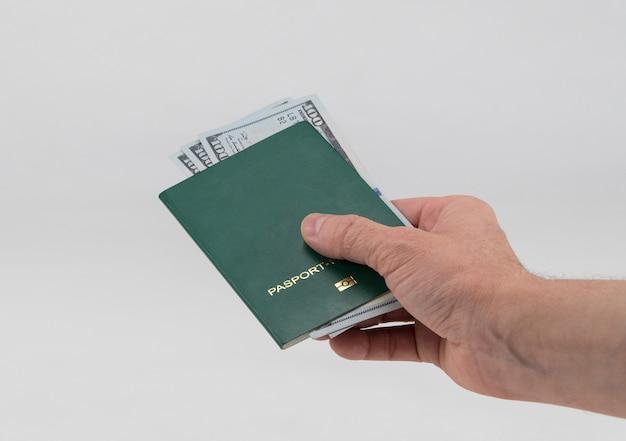Hand hält grünen pass mit us-dollar aus. konzept - bestechung und korruption