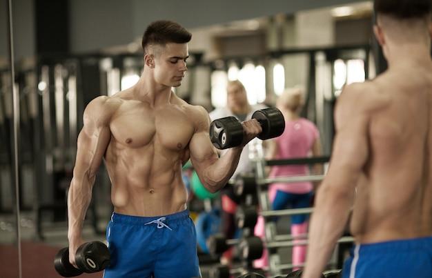 Hand hält hantel. schließen. muskulöser arm im fitnessstudio. training, sport, hand, hantel, training. - das konzept eines gesunden lebensstils und fitness. artikel über fitness und sport.