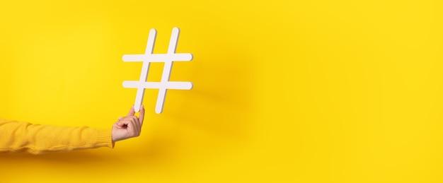 Hand hält hashtag-symbol, macht wichtiges thema populär, setzt trends im internet, panorama-modell
