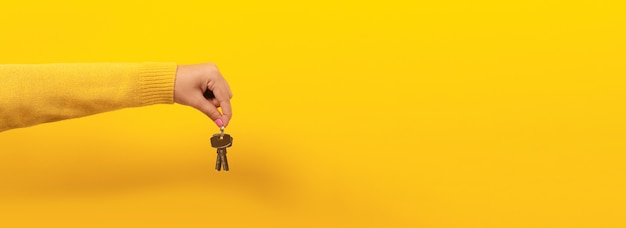Hand hält hausschlüssel und schlägt vor, über gelbem raum