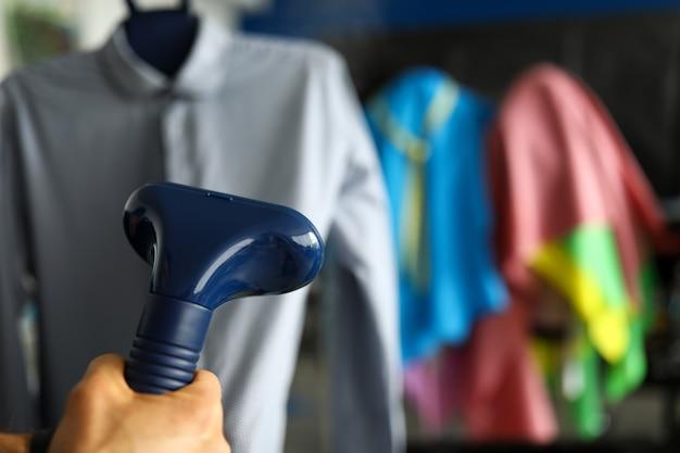 Hand hält heimkleidungsdampfer in der nähe von kleidung, nahaufnahme chemische reinigung von kleidung zu hause