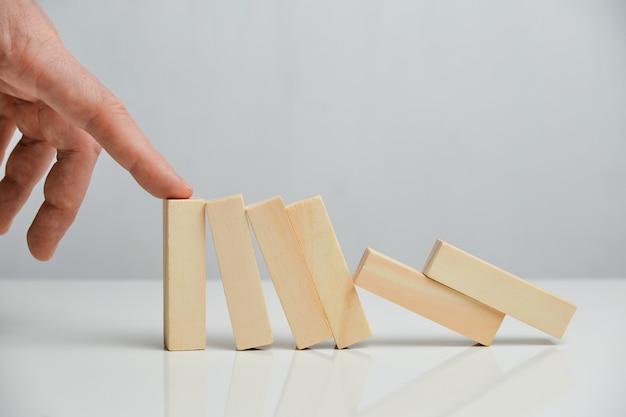 Hand hält holzklötze vor dem herunterfallen