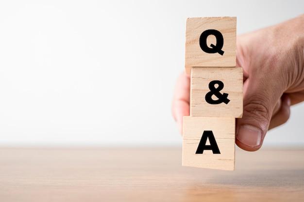 Hand hält holzwürfel für fragen und antworten oder fragen und antworten
