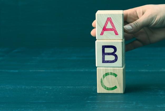 Hand hält holzwürfel mit buchstaben a, b, c.