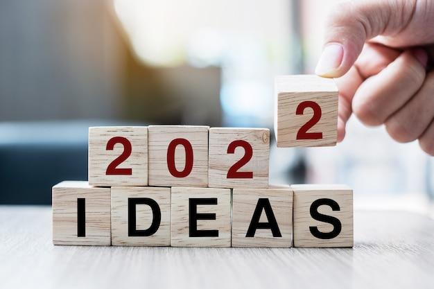 Hand hält holzwürfel mit flip-over-block 2022 ideen