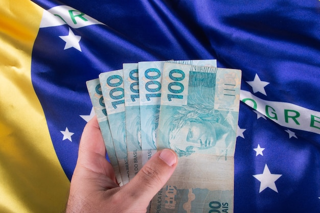 Hand hält hundert reais banknoten über brasilianischer flagge.
