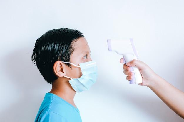 Hand hält infrarot-thermometer, das die temperatur des jungen mit medizinischer maske auf dem gesicht misst