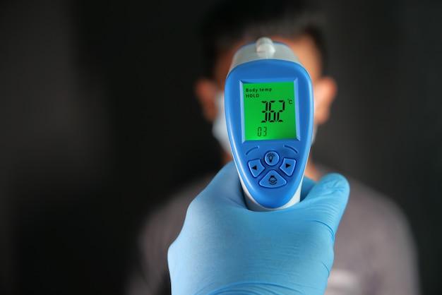 Hand hält infrarot-thermometer zur temperaturmessung.