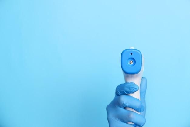 Hand hält infrarot-thermometer zur temperaturmessung