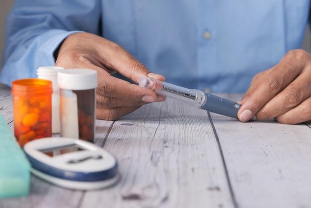 Hand hält insulinpens mit kopierraum, von oben nach unten