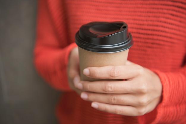 Hand hält kaffee pappbecher. mock-up für das branding.