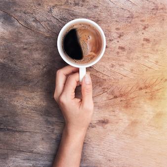 Hand hält kaffeetasse
