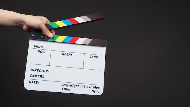 Hand hält klappe oder filmschiefer. es wird in der videoproduktion und filmindustrie auf schwarzem hintergrund verwendet.