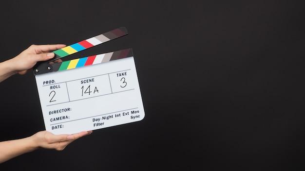 Hand hält klappe oder filmschiefer mit schreibnummer auf schwarzem hintergrund.