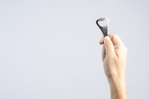 Hand hält klassischen flaschenöffner aus stahl