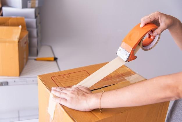Hand hält klebeband, um produkte zu verpacken, um sendungen vorzubereiten.
