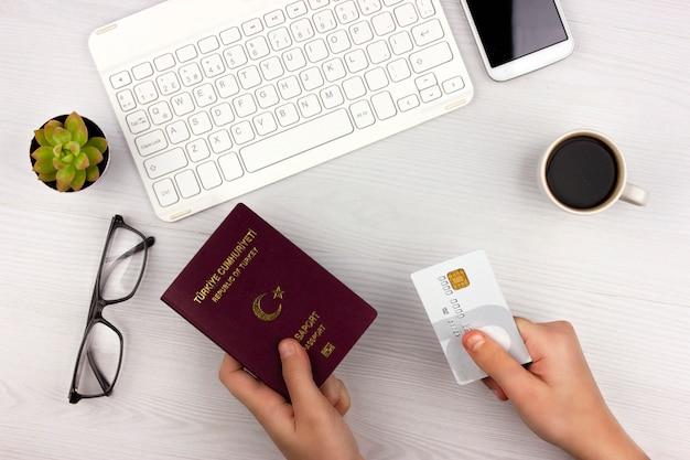 Hand hält kreditkarte für die online-buchung eines hotels und eines flugtickets