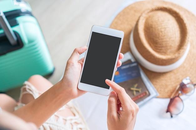 Hand hält kreditkarte während der verwendung des mobiltelefons mit reiseaccessoires auf dem bett.