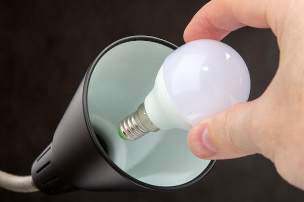 Hand hält led-lampe geringen stromverbrauch, austausch von glühbirnen in stehlampe, schwarz.