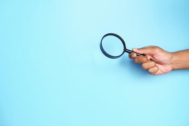 Hand hält lupe auf blau mit kopierraum