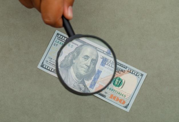 Hand hält lupe über banknote.