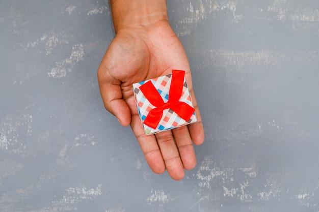 Hand hält mini-geschenkpaket.