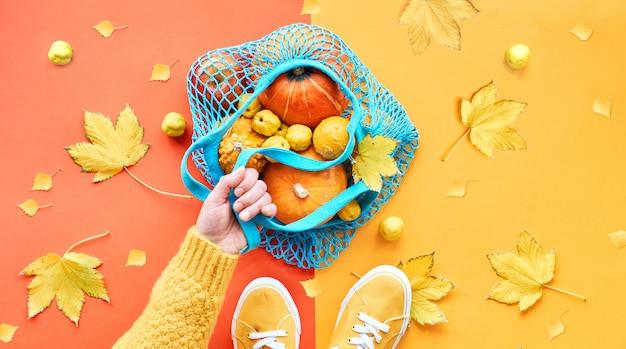 Hand hält orange kürbisse in blauem minzgitterbeutel, herbstspaltpapier flach lag in gelb und orange