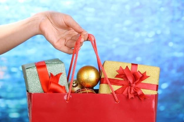 Hand hält paket mit weihnachtskugeln und geschenken