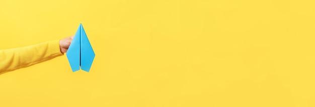 Hand hält papierflugzeug über gelb