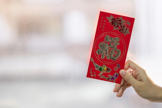 Hand hält roten umschlag oder ang pao. chinesisches mondneujahrsfeierkonzept, chinesisches wort bedeutet glück und erfolgreich