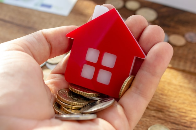 Hand hält rotes haus nach hause und geld immobilienkonzept, immobilienkosten, immobilienkosten, kauf einer immobilie