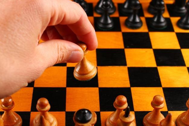 Hand hält schachfigur des bauern