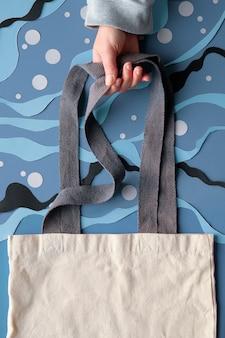Hand hält segeltuchtasche auf abstraktem meerunterwasserhintergrund vom geschnittenen papier. von matisse inspirierte collage zum schneiden von papier.