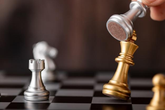 Hand hält silberkönig angriff goldführer im spiel