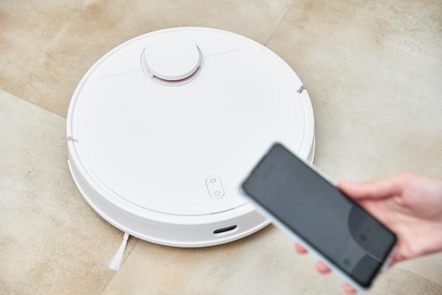 Hand hält smartphone mit anwendungssteuerungsroboter staubsauger