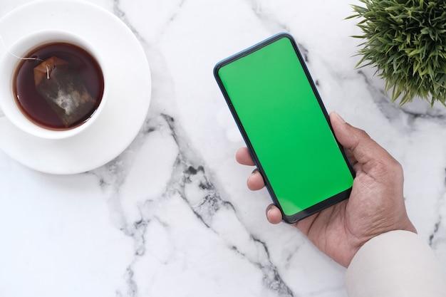 Hand hält smartphone mit leerem bildschirm auf kachel backgorund