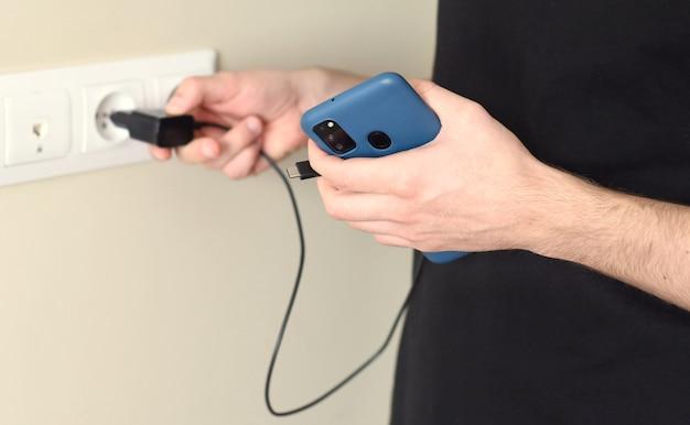 Hand hält smartphone und bereitet sich auf das aufladen vor