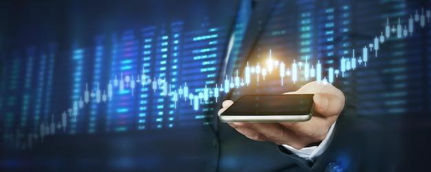 Hand hält smartphone und touchscreen. börsenkonzept. geschäftsmannhändler, der mit grafikanalysekerze zuschaut