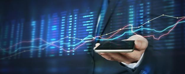 Hand hält smartphone und touchscreen. geschäftsmannhändler, der mit grafikanalysekerze zuschaut