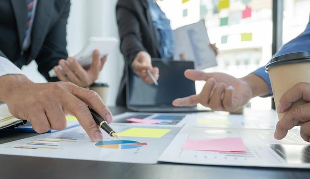 Hand hält stift, geschäftsfrauen und geschäftsleute treffen sich, um strategien zur steigerung des geschäftseinkommens zu planen. führen sie eine brainstorming-finanzdiagrammanalyse durch und diskutieren sie für den neuen zielerfolg.