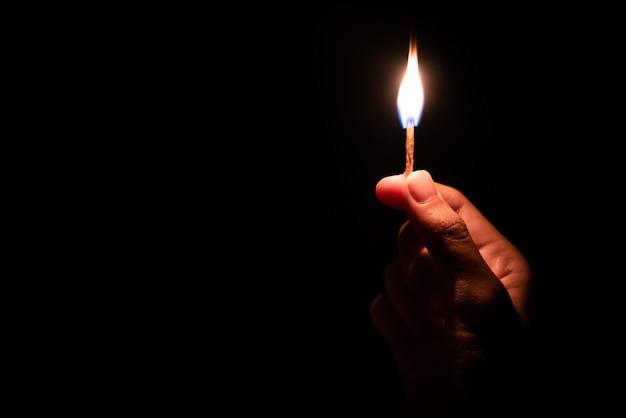 Hand hält streichholz im dunkeln
