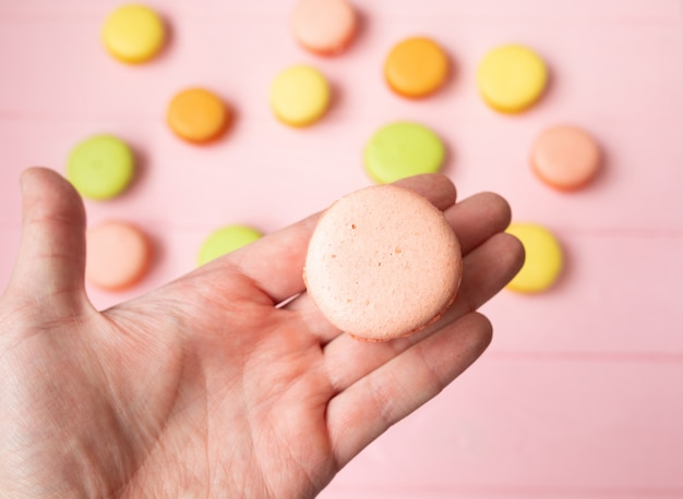 Hand hält süße und bunte französische makronen oder macaron auf rosa tisch