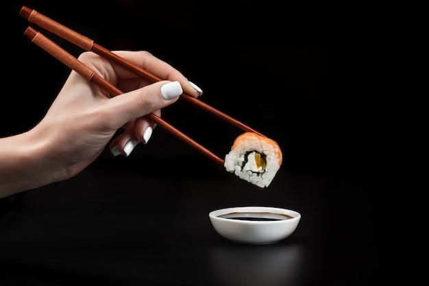 Hand hält sushi über schüssel mit sojasauce auf schwarzem tisch.