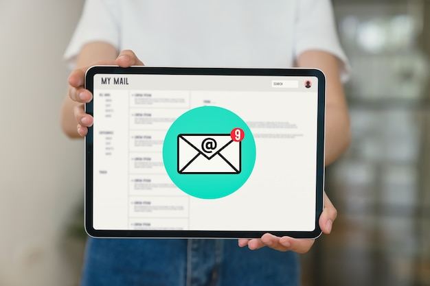 Hand hält tablett und zeigt e-mail-bildschirm auf anwendung handy im büro.