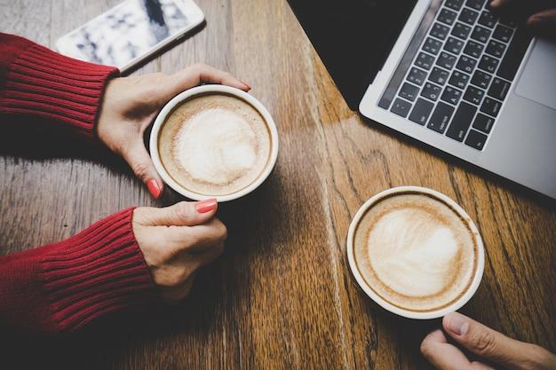 ็ hand hält tasse heißen latte kaffee und handy mit freund arbeiten