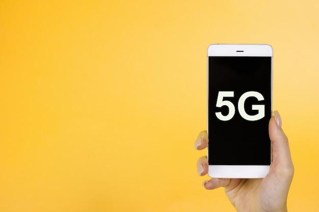 Hand hält telefon mit einem symbol 5g. das konzept des 5g-netzwerks, des mobilen hochgeschwindigkeitsinternets und der neuen generation