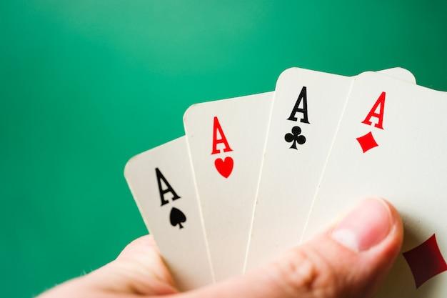 Hand hält vier asse auf einem grünen hintergrund.